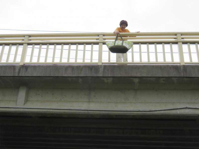橋の上から差し入れを落とす